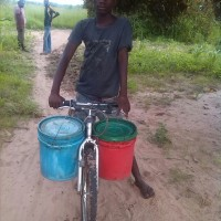 A young boy coming from fetching water