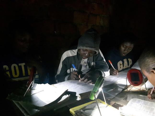 students studying by solar powered lights